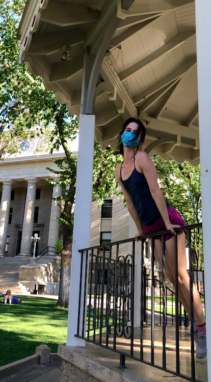 girl posing in front of courthouse plaza with green tank top and purple shorts