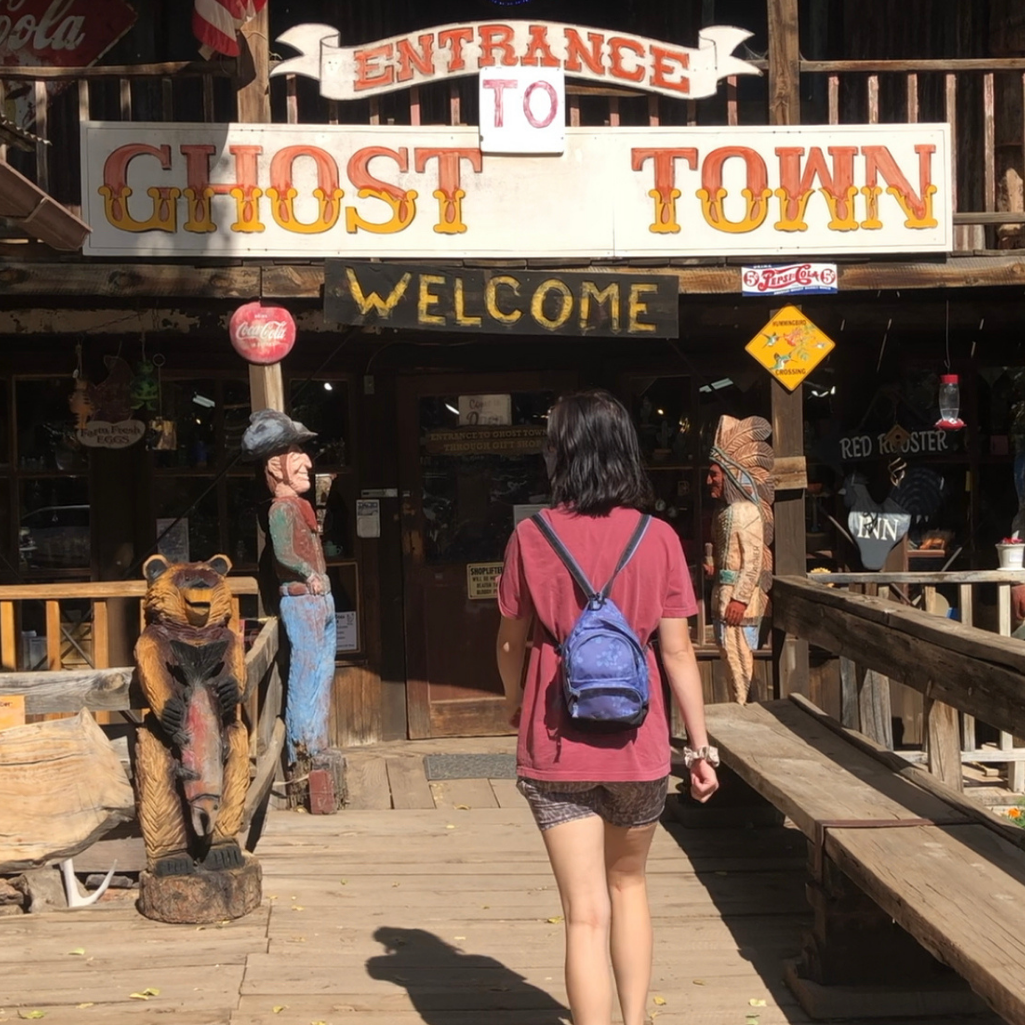 girl walking into tall wooden building with Gold King Mine & Ghost Town printed on the front