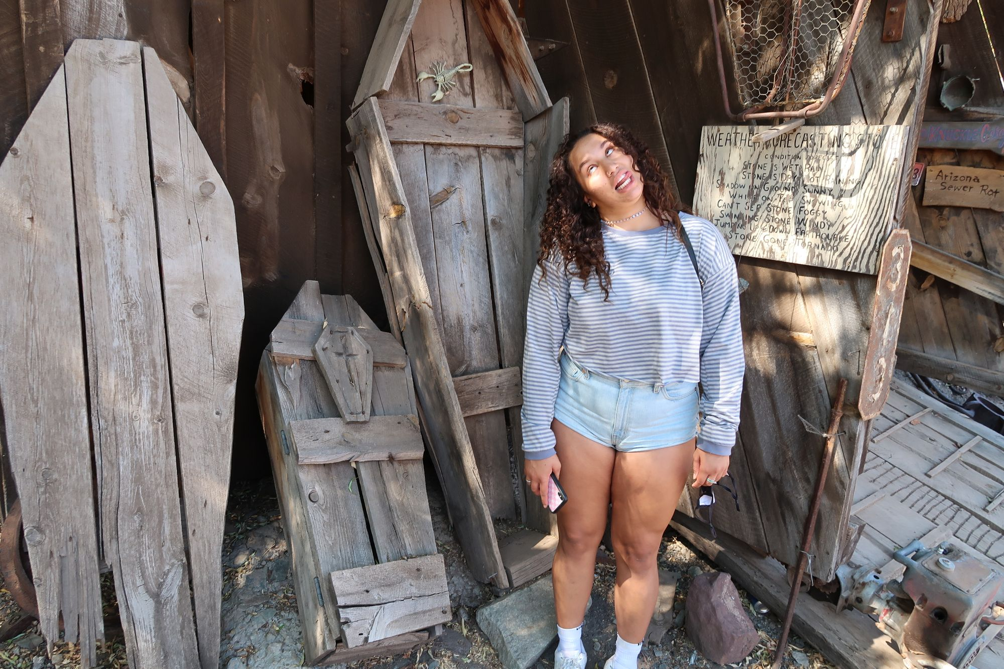 Girl posing with coffins at Ghost Town in Jerome, AZ