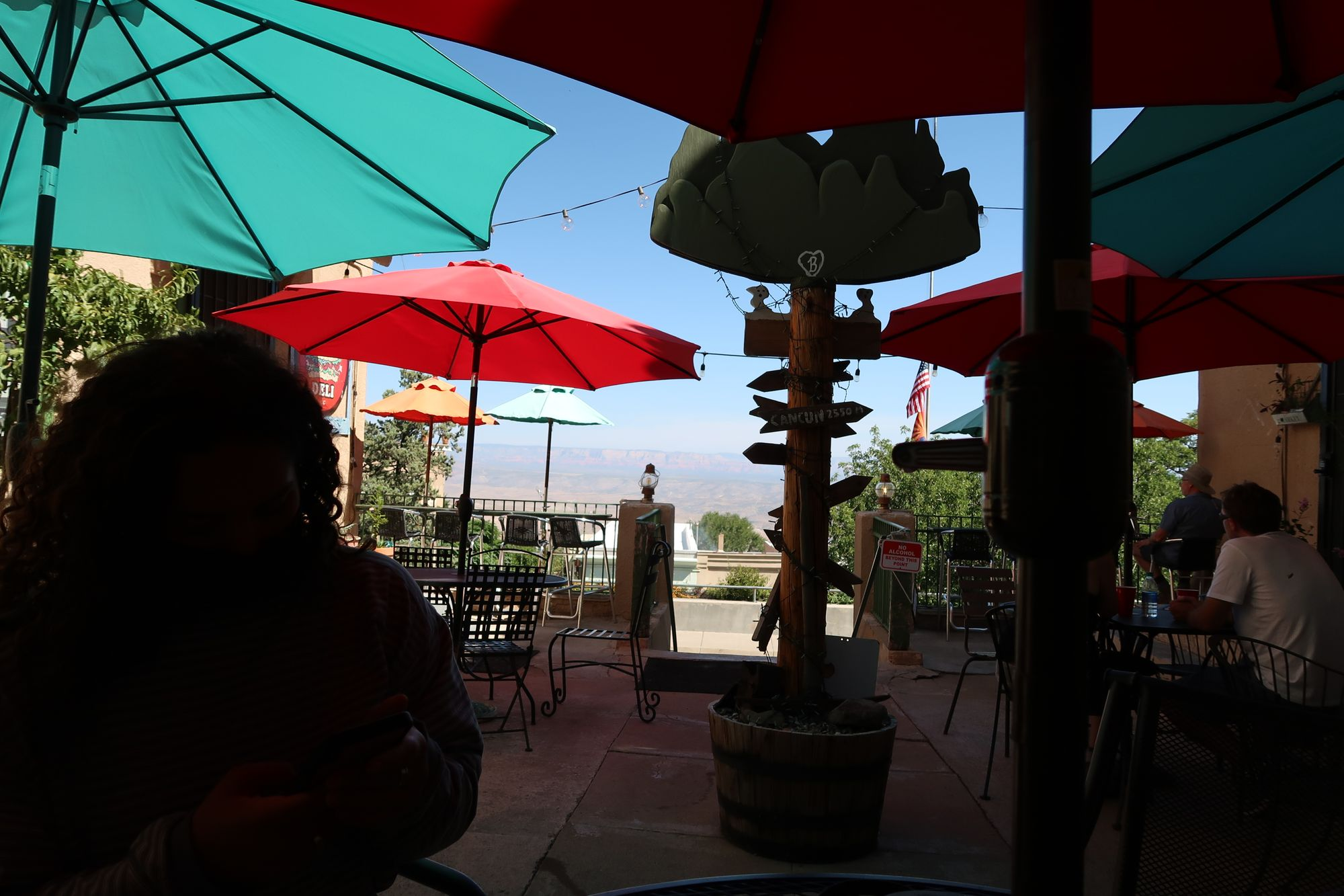 girl sitting in shadows of Hilltop Deli in Jerome Arizona with brighty colored umbrellas
