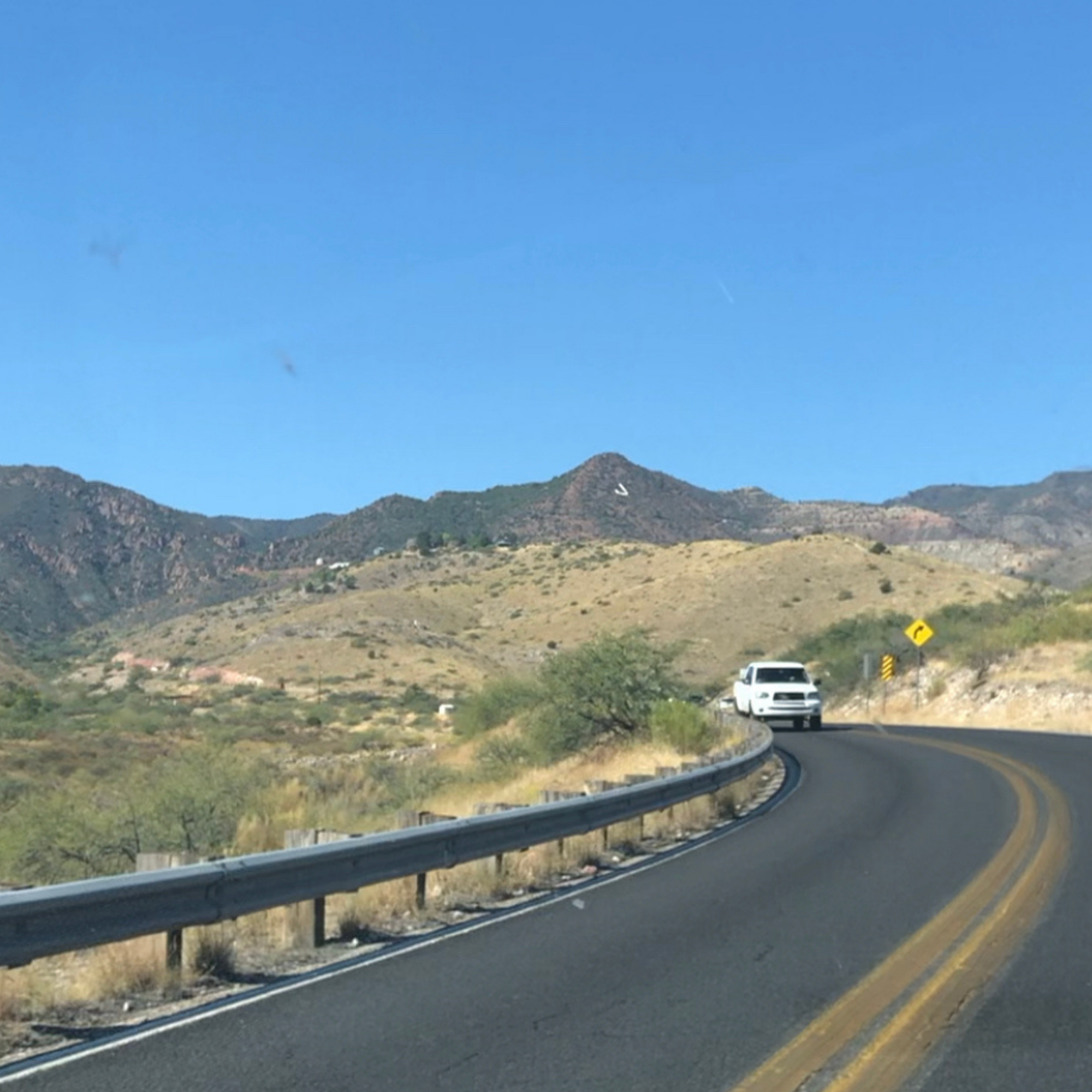 driving on road towards jerome arizona with the J on the side of the mountain