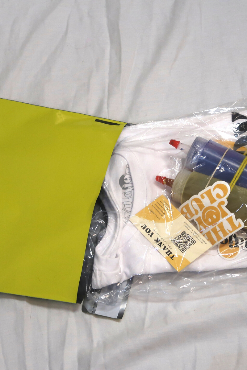 Yellow bag, plastic bag, tie-dye materials, thank you card, and bottles of dye