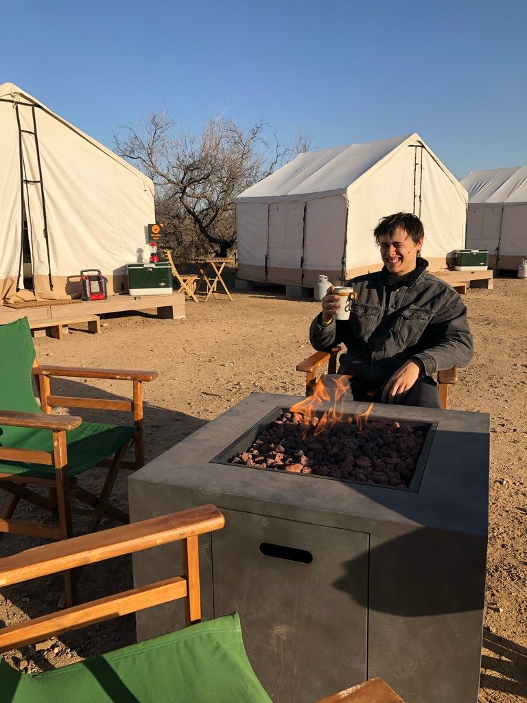 Man sitting at firepit glamping at Out of Africa in Arizona